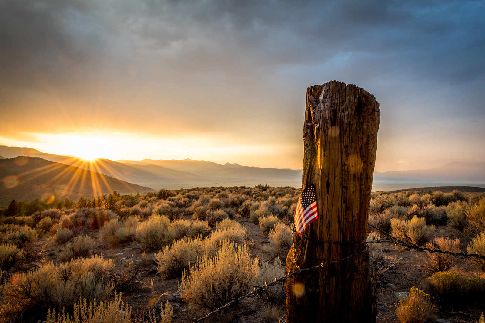 Sunset behind US Flag stuck in old log fence post with barb wire on lower Summer Meadows Road, CA